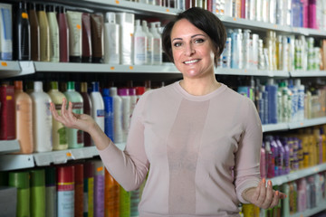 Happy female customer choosing conditioner for hair in beauty store