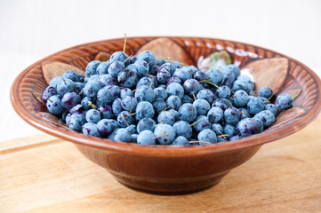 Berry blueberries in a ceramic bowl on table