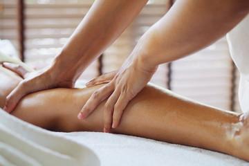 Therapist doing massage foot massage in spa treatment room.