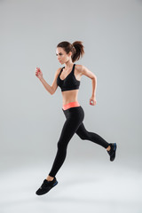 Full length image of a sports woman running in studio