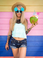Beautiful young blonde hipster in denim shorts and a straw hat, sunglasses stands amid the brightly colored walls with a coconut in hand. Tropical weekend, beach party.
