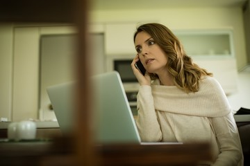 Woman talking on phone while using laptop computer
