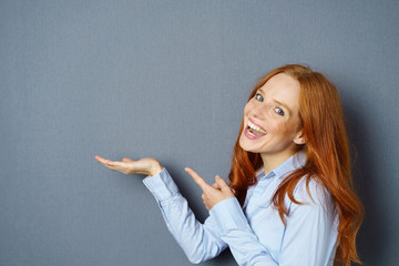 lachende frau zeigt mit dem finger auf etwas in ihrer hand