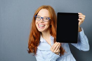 lächelnde frau präsentiert etwas am tablet