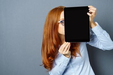frau versteckt sich hinter tablet