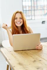 glückliche junge frau arbeitet zuhause am notebook