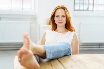 entspannte frau legt die füße auf den tisch