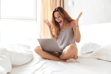 Happy woman using laptop in the morning