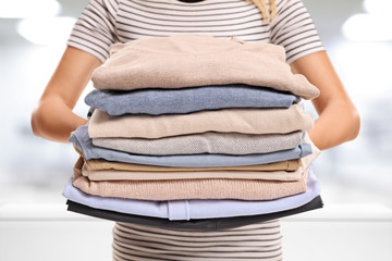 Woman with pile of ironed and packed clothes