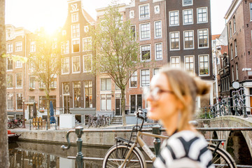 Stores à enrouleur Amsterdam Lifestyle portrait of a woman walking with bouquet of pink tulips near the water channel in Amsterdam city. Woman is out of focus