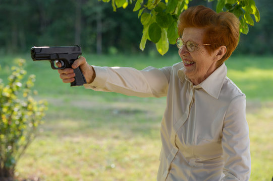 woman in glasses holds a pistol in the open air.