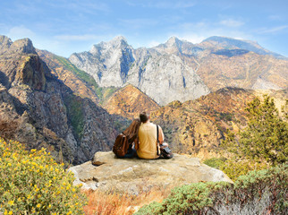 Couple looking at beautiful coastal mountain landscape on hiking trip. Kings Canyon National Park, Fresno, California, USA