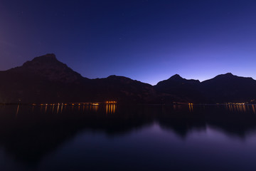 Lake. Night. Night panorama. Mountains, lake, reflection of lights in the water. Switzerland. Canton of Uri.
