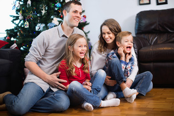 Young happy family sitting by Christmas tree at home