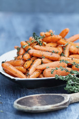 Honey Glazed Baby carrots with wooden spoon. Extreme shallow depth of field with selective focus on carrots in foreground of dish.