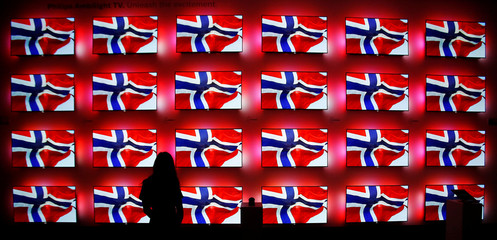 A woman stands in front of a wall with Philips ambient light flat screens at the IFA Electronics show in Berlin