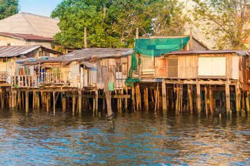 Stilt houses along the Chao Phraya river in the megacity Bangkok. In many parts, the simple houses have been demolished and are replaced from expensive apartments