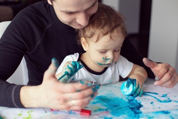 Father and little boy having fun painting at home