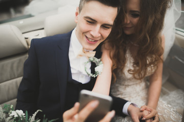 Happy groom is taking selfie with his pretty bride on wedding day