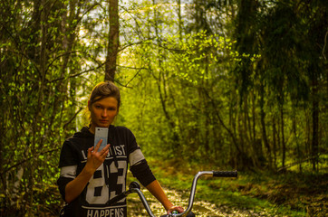 Attractive woman with bicycle using phone in forest