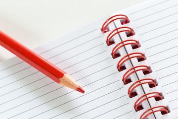 Pastello rosso su notes a righe con spirale rossa