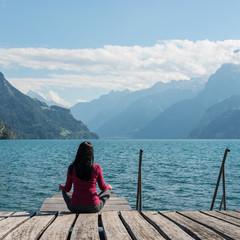 Meditation, self-reflection. Woman meditating sitting on the lake shore.