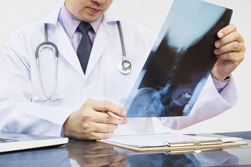 Doctor examine x-ray film over white background