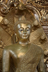 Antique gold Buddha statue covered in golden robes at temple in Myanmar.