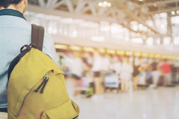 Soft focused picture of traveler over blurred long passenger queue waiting for check-in at airport check-in counters