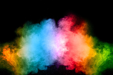The explosion of multi colored powder. Beautiful powder fly away. The cloud of glowing color powder on white background
