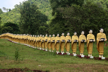 Simulated statue that's like a monk holding a almsbowl lined up beautiful at the temple in Myanmar.