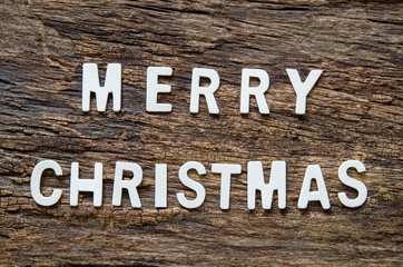 Merry Christmas wording on wooden background.