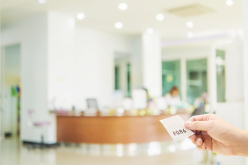 Man is holding queue card while waiting in the modern reception area