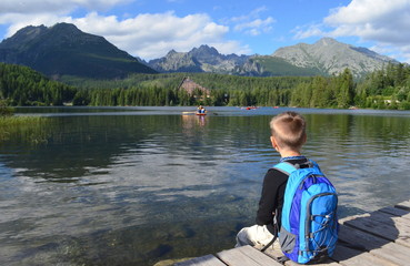 A young boy hiker with a backpack on his back sits by the lake looking on the mountains landscape (Strbske Pleso lake, Hight Tatras mountains, Slovakia, Europe)