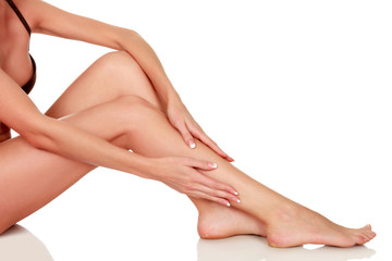 Woman's legs with clean and smooth skin on white background, isolated
