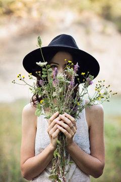 Giovane donna che sorriede nascosta da un mazzo di fiori di campo