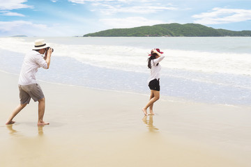 Couple on beach taking photo happily during their vacation in Rayong, Thailand