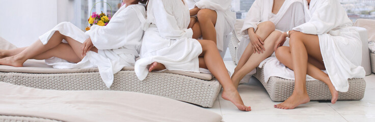 Poster de jardin Spa Group of woman in robes Womens legs in the spa