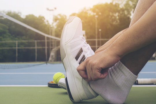 Tennis player is putting shoe before the match in tennis hard court