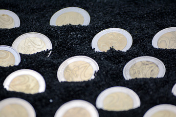 Euro coins in black sand close up photo