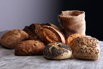 Different kinds of bread and bread rolls on board. Kitchen or bakery poster design.