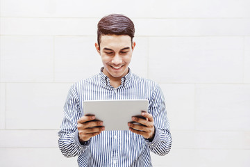 Asian Happiness Businessman or Student Smile while Read or Working on a digital Tablet outside Office Building