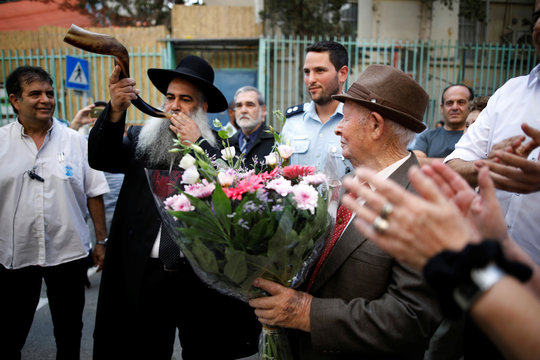 Shalom Shtamberg, a 93-year old Holocaust survivor, listens as a rabbi blows the Shofar, as part of celebrations marking his bar mitzvah ceremony, in Haifa
