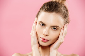 Beauty Spa Concept - Caucasian Woman with perfect face skin Portrait. Beautiful Brunette Spa Girl showing empty copy space. Isolated on pink studio background. Proposing a product.