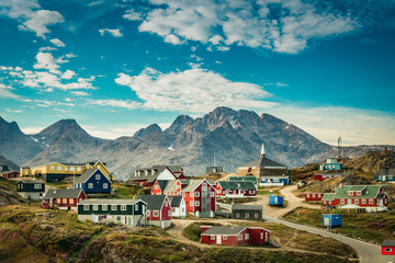 Small town on east coast of Greenland with colorful houses and mountain background Wall mural