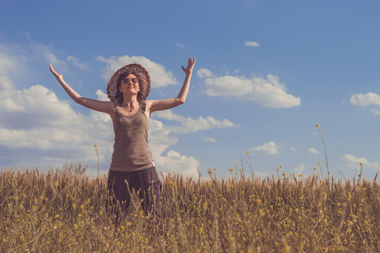 Young woman with hat enjoying the nature. Freedom concept.