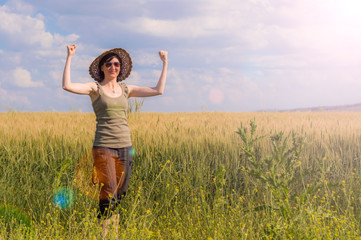 Young woman with hat enjoying the nature. Victory concept.