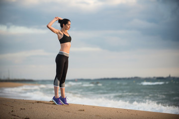 A young woman wearing sportswear is doing stretches on the beach