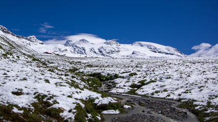 Panoramic view of a small river with beautiful mountain landscape in the background. Summer in the Pennine Alps, Valle d'Aosta, Italy, Europe.