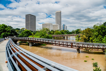 High and fast water rising in Bayou River from Rosemont pedestrian bridge with near town Houston in background, cloud blue sky. Heavy rains from Harvey Tropical Hurricane storm caused many flood areas